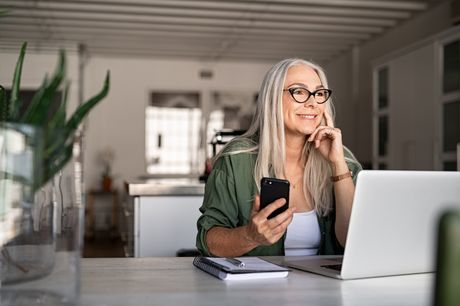 Senior woman using a laptop and smartphone in her home