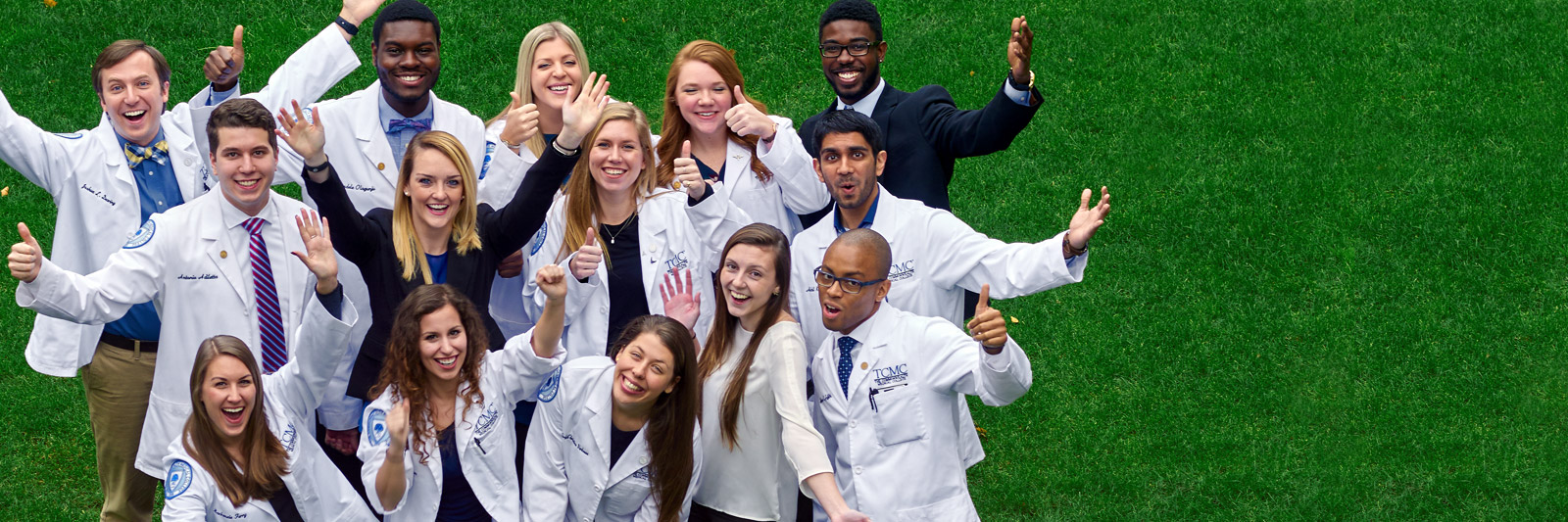 Geisinger Commonwealth students on grass field with arms raised