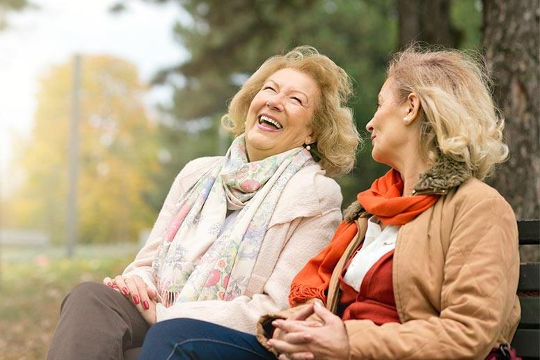 two aging women laughing on a park bench