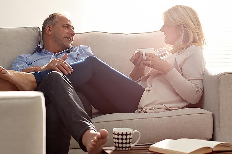 Relaxed couple on couch discussing options for liposuction