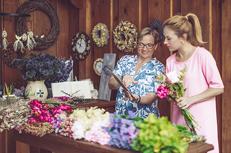 Tow women working together at a flower shop one lady is wearing glasses.