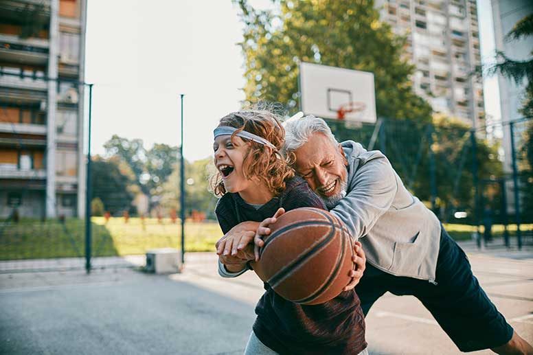 Grandfather and Grandson laughing playing basketball