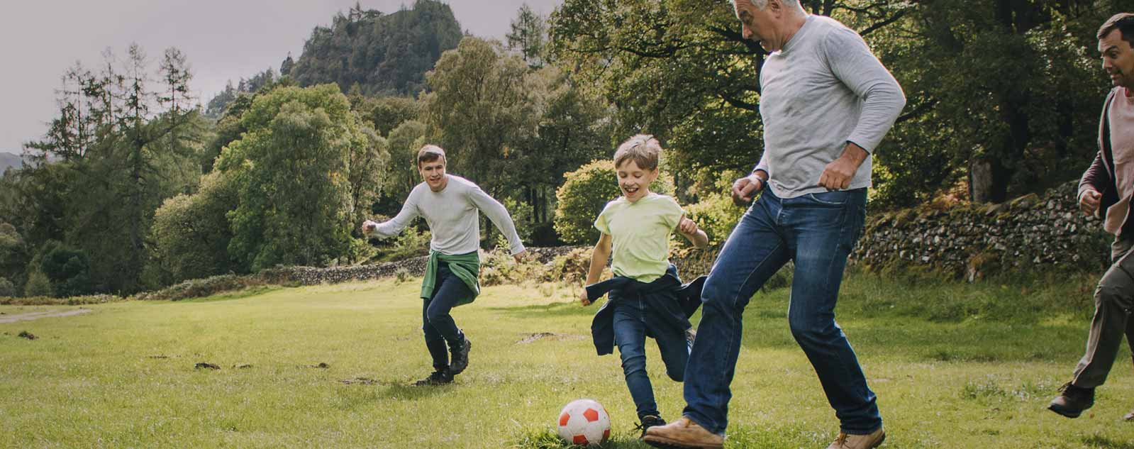 Family in a field playing soccer after working with Geisinger orthopaedic care