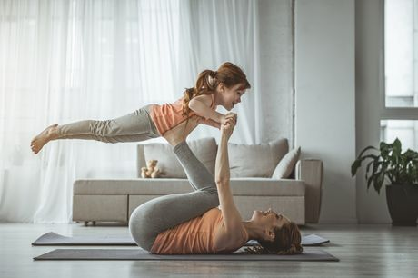 Woman on a yoga mat in a living room lifting her child.
