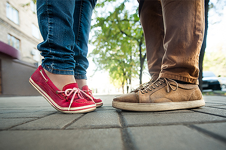 Image of teenagers feet standing on a sidewalk