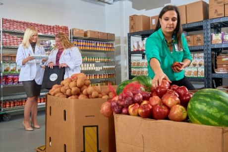 Geisinger Fresh Food Farmacy staffers organize and discuss fruits and vegetables.
