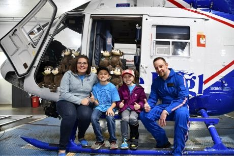 Kristy Creasy, Tyler Creasy, Aly Creasy and Scott Lynn sitting on the leg of a helicopter.