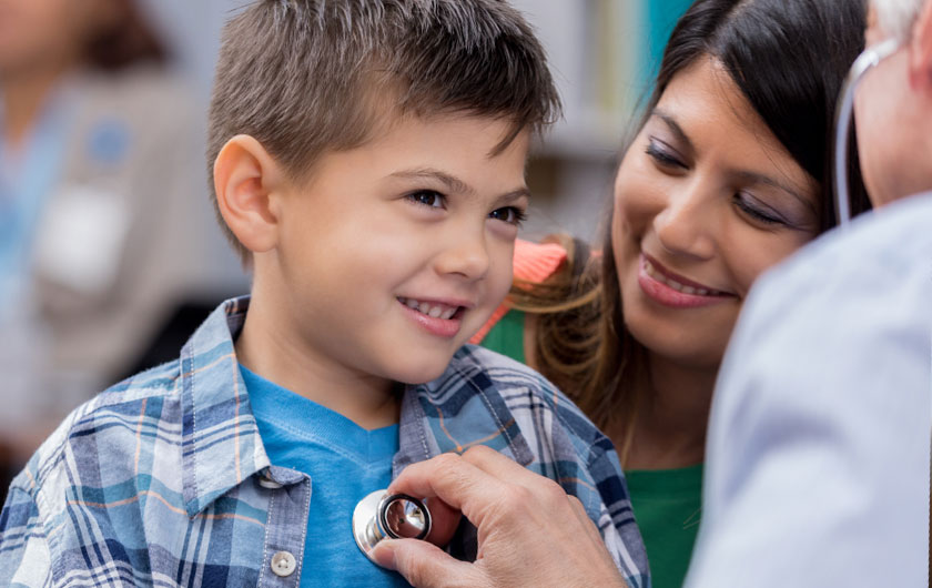 Doctor examining young boy in outpatient setting