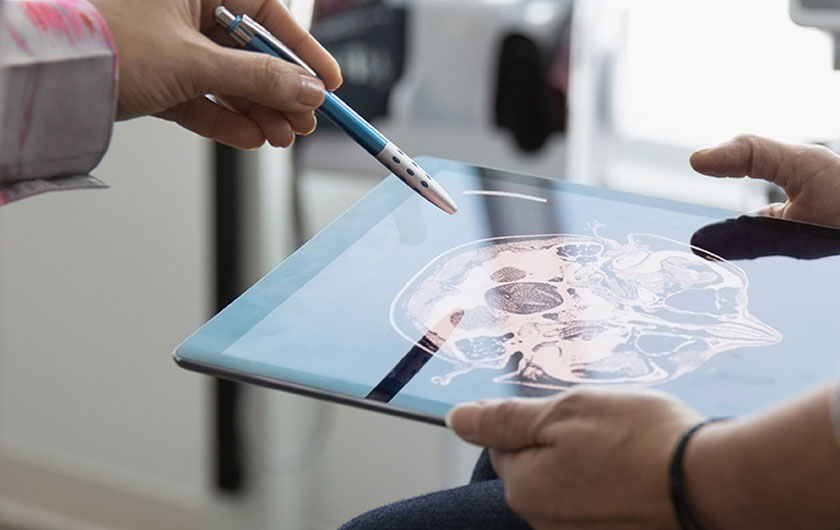 Doctors looking at brain scans on tablet device