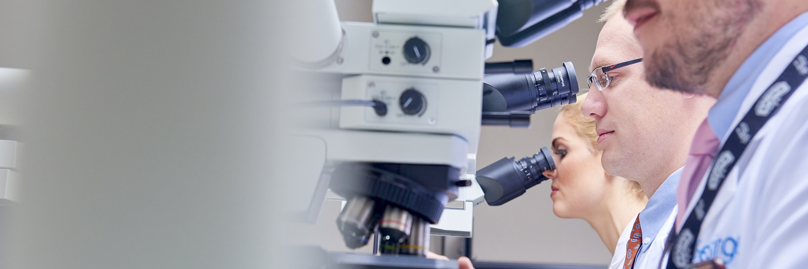 Three doctors look through microscopes