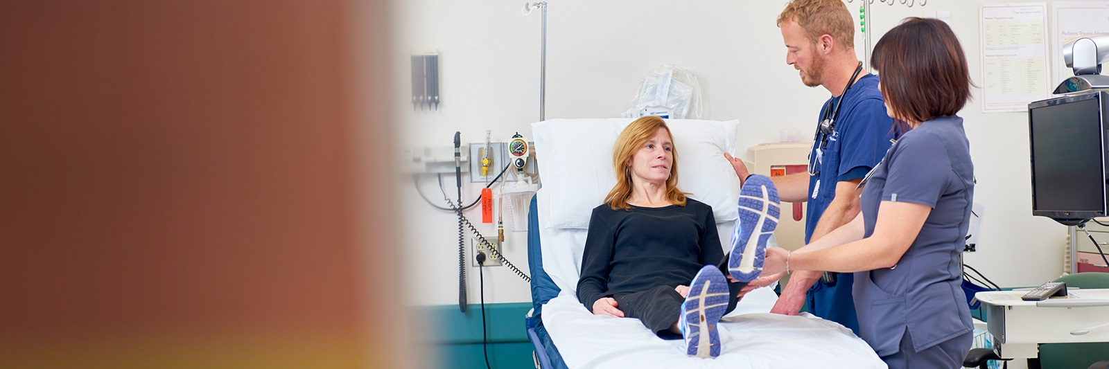 Woman raising one leg in bed as two healthcare providers look on
