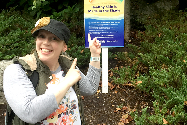 Woman pointing at sign outdoors that says healthy skin is made in the shade