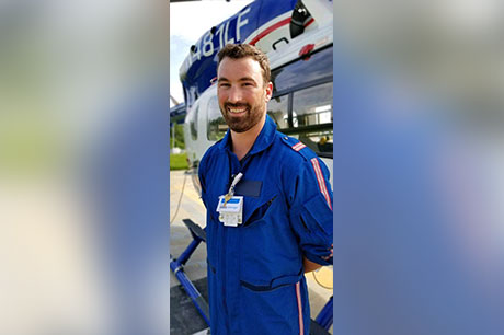 Alex Haines, RN, flight nurse with Geisinger LifeFlight, stands next to the LifeFlight helicopter.
