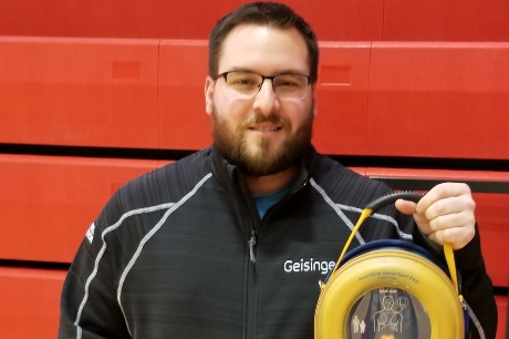 Geisinger certified athletic trainer Joseph Rosell with his automated external defibrillator (AED).