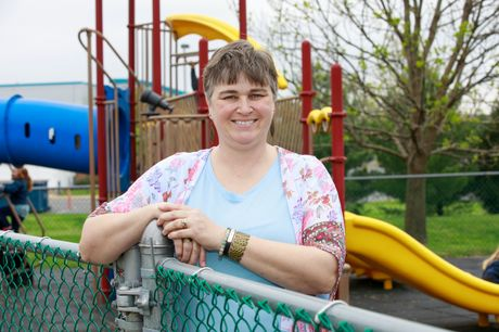 Leslie Sheaffer of Reedsville standing at a fence in a children's playground after her hip replacement surgery.