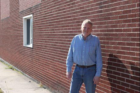 Bob Lepley stands in front of a brick wall, smiling.