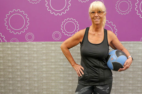 Bonnie Traugh standing in the gym, holding a medicine ball at her hip.
