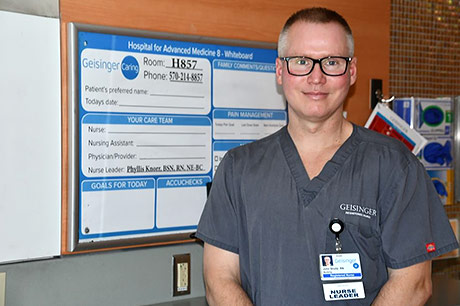 John, a cardiac nurse, stands in the hospital near a patient board.
