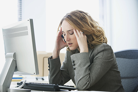 Stressed out woman sits at computer rubbing her temples