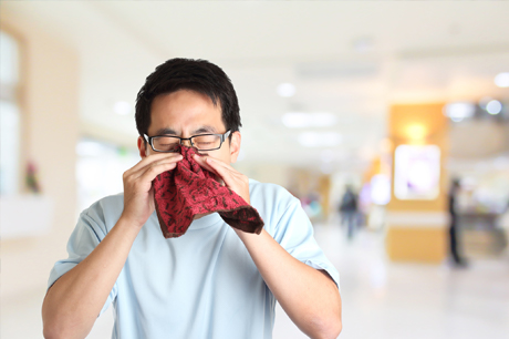 Man sneezing in handkerchief