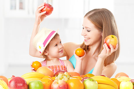 mom with daughter holding fruit
