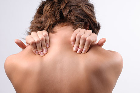 Woman squeezing shoulders in pain