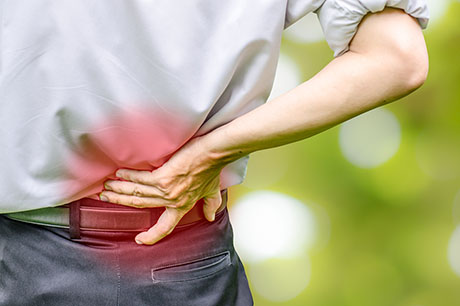 Person holding lower back in pain