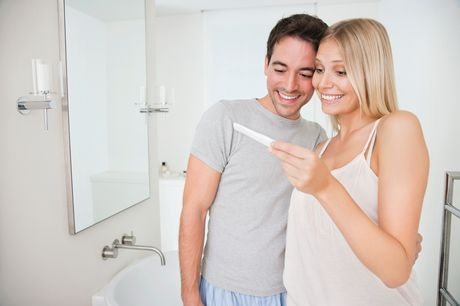 Happy couple in bathroom looking at pregnancy test.