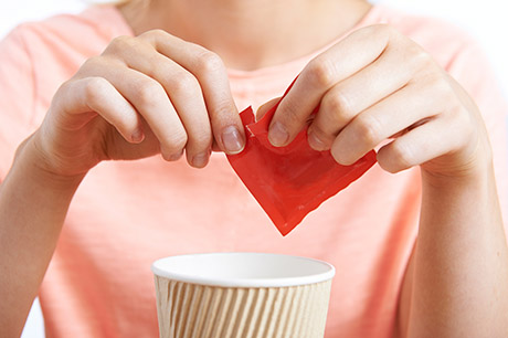 Women opening sugar packet
