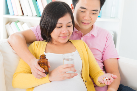 Pregnant woman and partner looking at medications