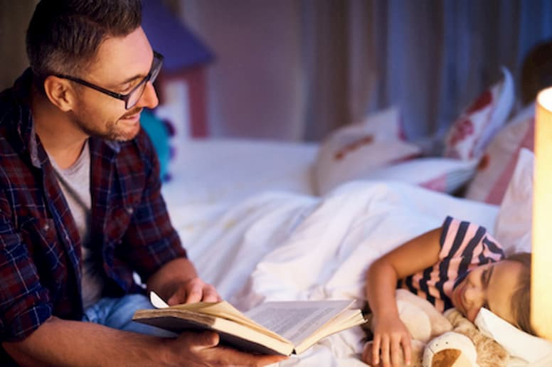 Man reading girl book at bedtime.