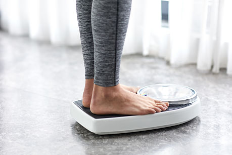 Person standing on scale for diet and weight loss