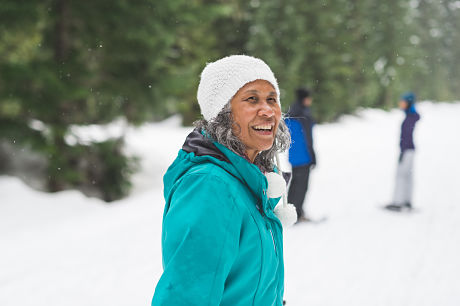 Elderly woman bundled up in the snow to stay warm and help prevent joint pain.