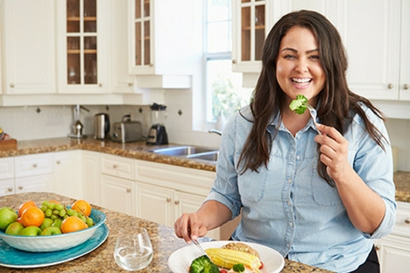 Woman smiling eating broccoli