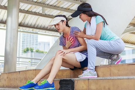 Two women in workout outfits sit on the steps. One is clutching her heart. The other tries to help.