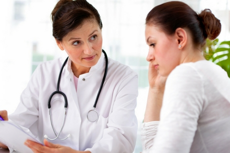 Female doctor reviewing chart with young woman patient