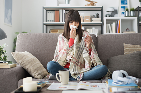 Woman blows nose on the couch