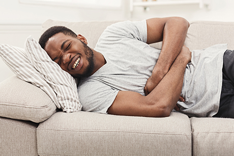Man on couch holding stomach