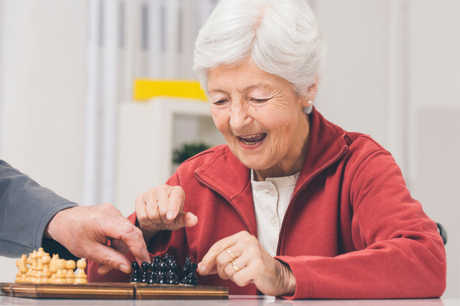 Elderly woman playing chess.