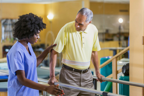 Man walks with assistance in physical therapy