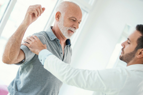 Man with shoulder injury being examined by doctor