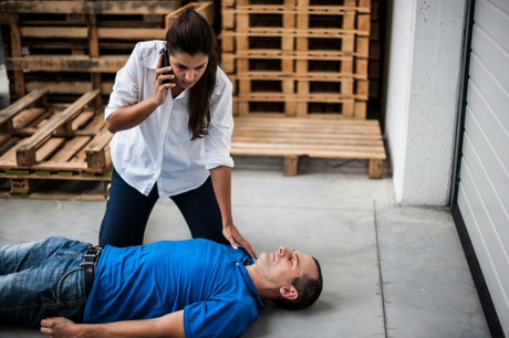 Man laying on the ground with woman on the phone over him.