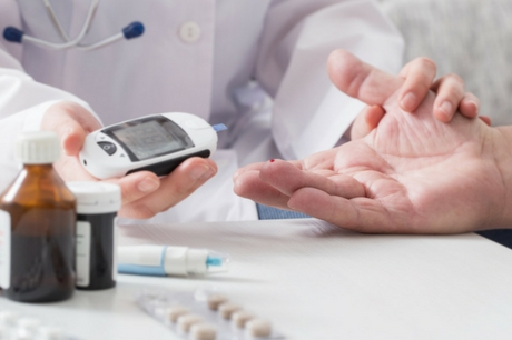 Doctor takes blood sugar level from a patient