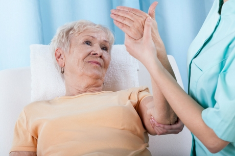 Elderly woman has her arm examined.