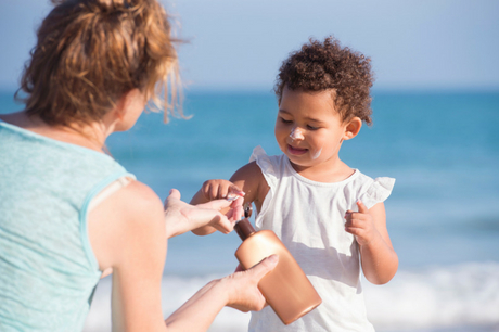 Woman putting sunscreen on a toddler.
