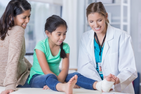 Doctor treating girl who has an ankle injury