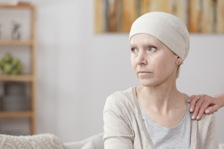 Woman looking out of frame with cancer diagnosis.