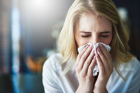 Sick woman with cold or flu blowing nose