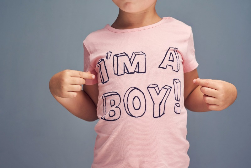 Child wearing pink t-shirt that says 'I'm a boy.'
