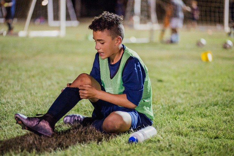 Injured child holding shin while sitting on soccer field.